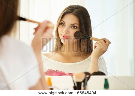 Beauty woman applying makeup. Beautiful girl looking in the mirror and applying cosmetic with a big brush. Girl gets blush on the cheekbones. Powder, rouge  poster
