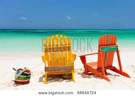 Colorful yellow and orange lounge chairs at tropical beach in Caribbean with beautiful turquoise ocean water, white sand and blue sky