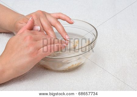 Hands in water with seashells