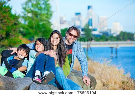 Disabled Boy In Wheelchair With Family Outdoors On Sunny Day, With City Skyline In Background