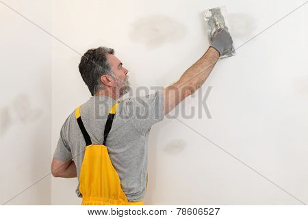 Worker Repairing Plaster At Wall