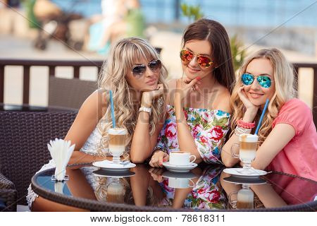 Three friends drinking coffee at a local cafe.