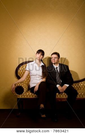 Young Beautiful Woman And Businessman In Suit Sitting On Sofa