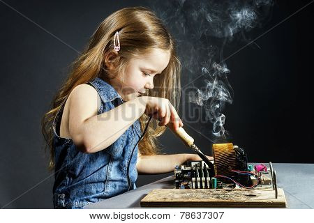 Cute little girl helping father to repair old computer motherboard using solderer poster