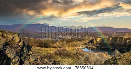Lake In Mountains Quarry Near City With Rainbow