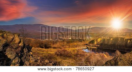 Lake In Mountains Quarry Near City At Sunset