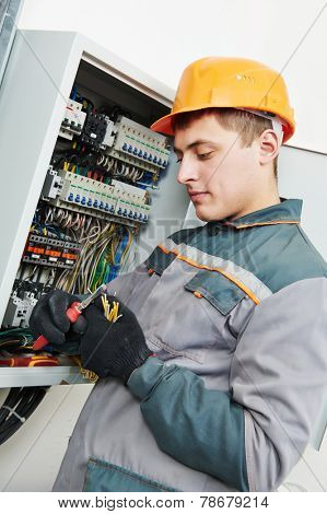 electrician builder engineer worker working with cable in fuse switch box