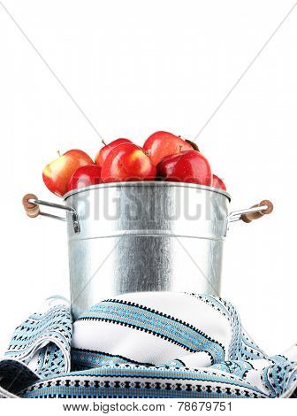 Pail filled with red apples and dishcloth on light background