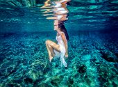 Beautiful dance underwater, gorgeous sportive woman wearing long white dress, dive to clear blue sea, zen balance and meditation concept poster