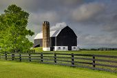 Beautiful rural Ontario scene showing a well kept black barn and farm. poster