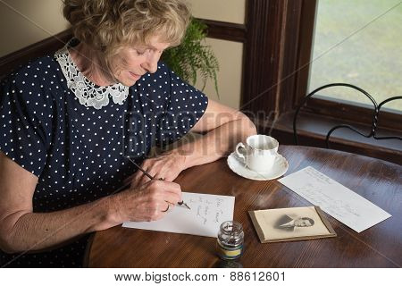 In a historical scene from the 1930's or 1940's an attractive elderly woman writes a letter as she sits at a table by a window. poster