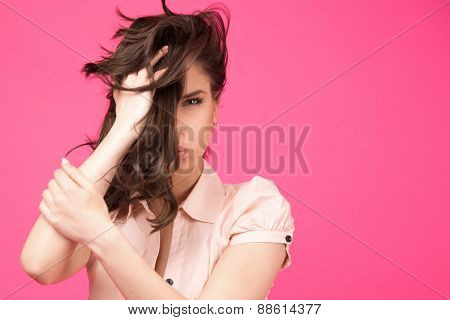 Beautiful woman holding her hair over pink background. Covering half face with hair. Looking at camera.