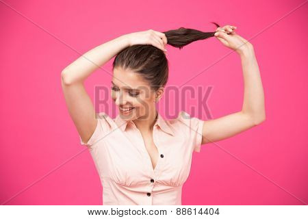 Happy young woman making her hair over pink background.