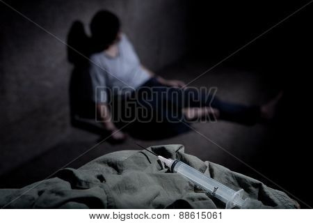 Closeup of syringe with man slumped against wall in dark alley