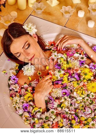 Woman relaxing at water spa. Aqueous surface covers many small flowers.