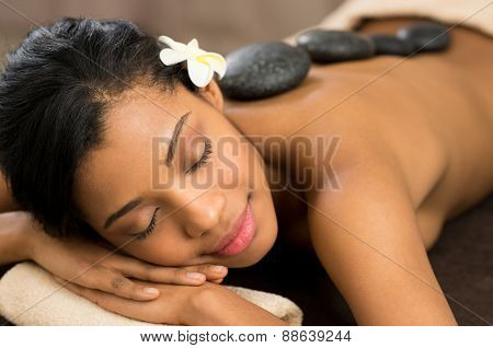 Beautiful young woman with eyes closed receiving hot stone massage at salon spa poster