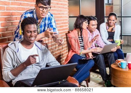 Computer programmer in start-up company coding, co-worker is looking over his shoulder
