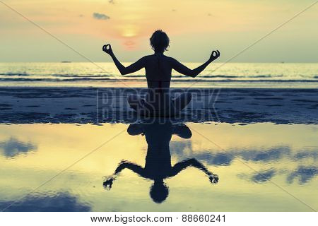 Silhouette of yoga woman meditating on the ocean beach. Fitness and Yoga.