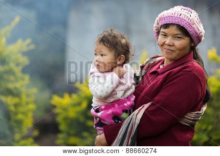 MAE KLANG LUANG, THAILAND, DECEMBER 31, 2014: A Karen tribe woman in traditional clothes with her kid in the village of Mae Klang Luang in the Doi Inthanon national park near Chiang Mai, Thailand