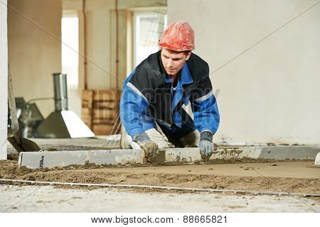 Plasterer doing indoors concrete cement floor topping with float