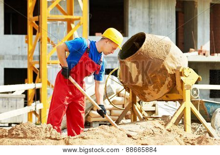 builder man working with shovel during concrete cement solution mortar preparation in mixer at construction site poster