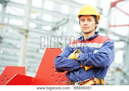 builder worker in uniform and safety protective equipment at construction site in front of metal construction frames poster