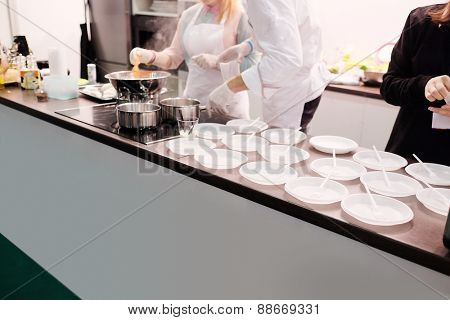 Chefs preparing food, empty plastic plates on the rack in a makeshift cafe poster