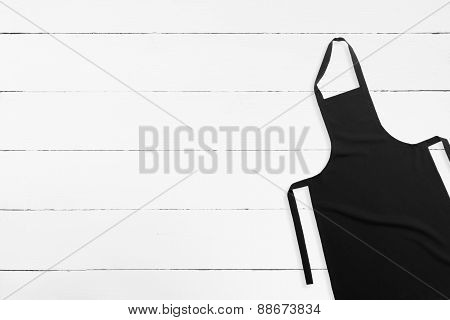 Blank black apron on white wooden background with copy space poster
