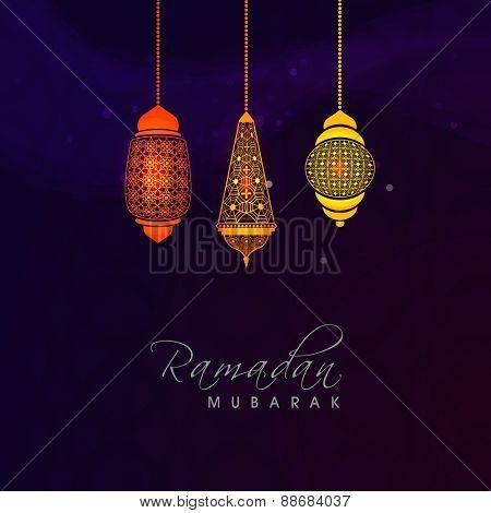 Colorful illuminated arabic lamps or lanterns on shiny purple background for holy month of muslim community, Ramadan Kareem celebration.