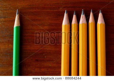 Five yellow pencils and one green pencil