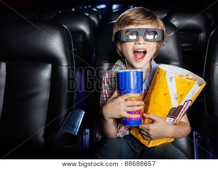 Surprised boy holding snacks while watching 3D movie in cinema theater poster