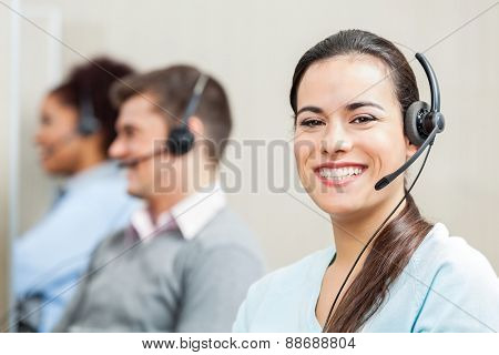 Portrait of smiling female customer service agent with colleagues in background at office