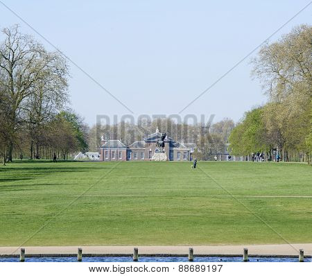 LONDON, UK - APRIL 22: Kensington Palace seen from the Serpentine lake on a sunny spring day, with George Frederic Watts's equine sculpture Physical Energy in the frame. April 22, 2015 in London.