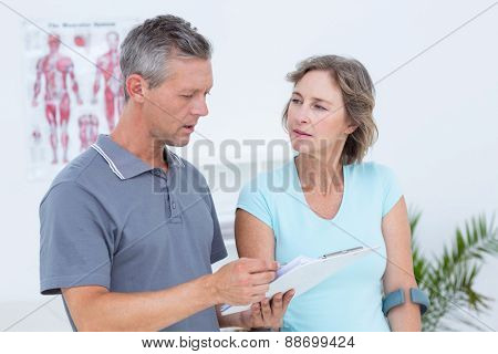 Woman using crutch and talking with her doctor in medical office