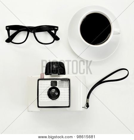 high-angle shot of a white table with a pair of black plastic-rimmed eyeglasses, a cup of coffee and an old instant camera