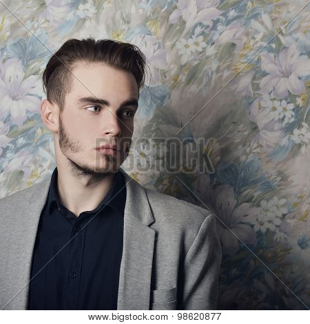 Portrait of attractive young mysterious man looking right at copy space, over floral background. Image toned.