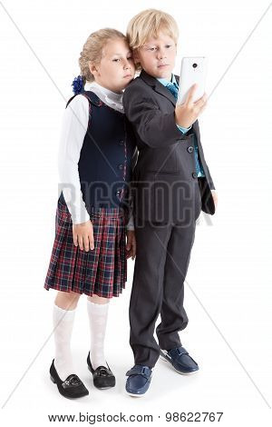 Full Length Of Pupils In Uniform Making Selfie Picture With Cellphone Together, Isolated On White Ba