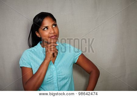 Charismatic girl planning with one hand on her chin while looking away against grey background poster