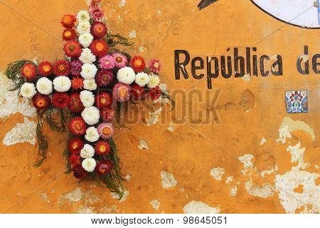 Folk style flower wreath on weathered orange wall in Guatemala City