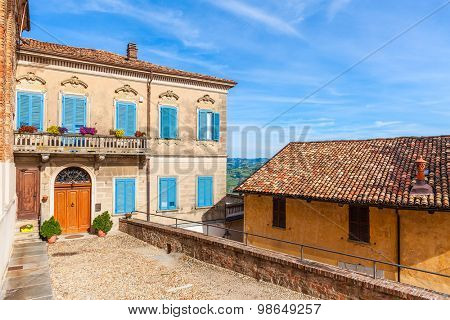Facade of colorful house with wooden shutters under blue sky in small italian town in Piedmont, Northern Italy.