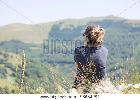 Young Woman With Backpack Sitting On Cliff's Edge And Looking To Mountains And Clear Sky. Hiking Tri