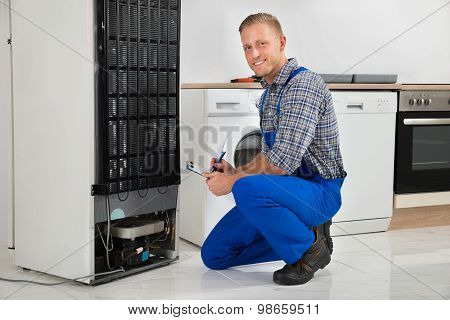 Plumber Writing On Clipboard In Front Of Refrigerator