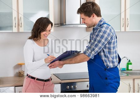 Woman Writing On Clipboard In Front Of Plumber