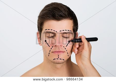 Person Hands Making Lines On Face Of Man