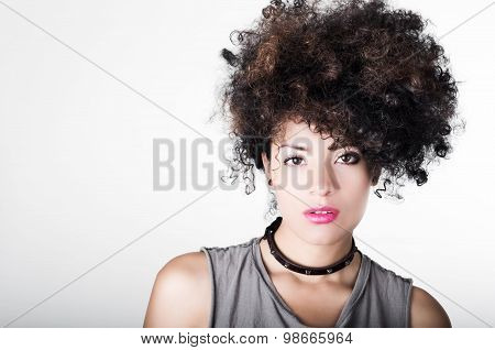 Headshot brunette hispanic model afro like hair dark eyes black necklace posing for camera