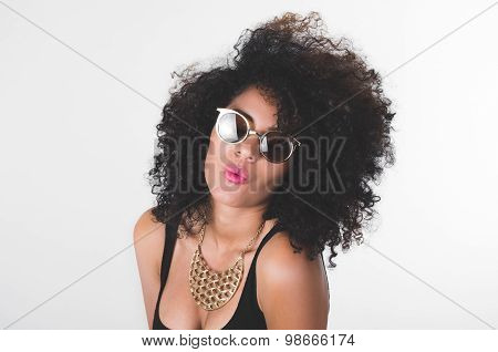 Headshot hispanic model wearing black dress, golden necklace, sunglasses and curly hair making kiss