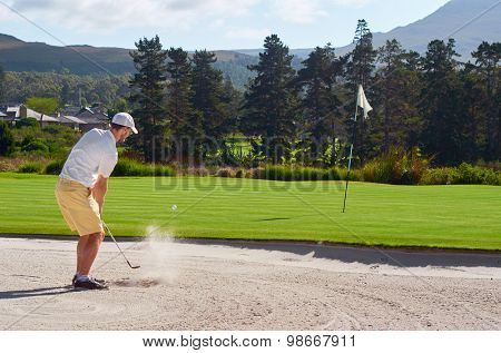 golfer playing a sand shot from bunker hazard