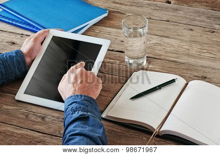 an holding tablet computer and click on the screen