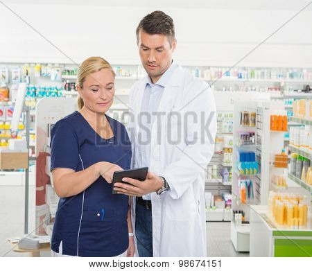 Female assistant using tablet computer with male pharmacist while standing in pharmacy