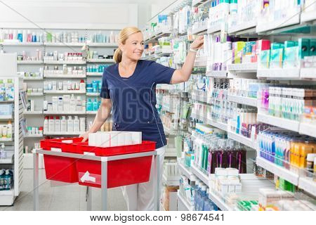 Smiling mature female chemist arranging products in pharmacy poster